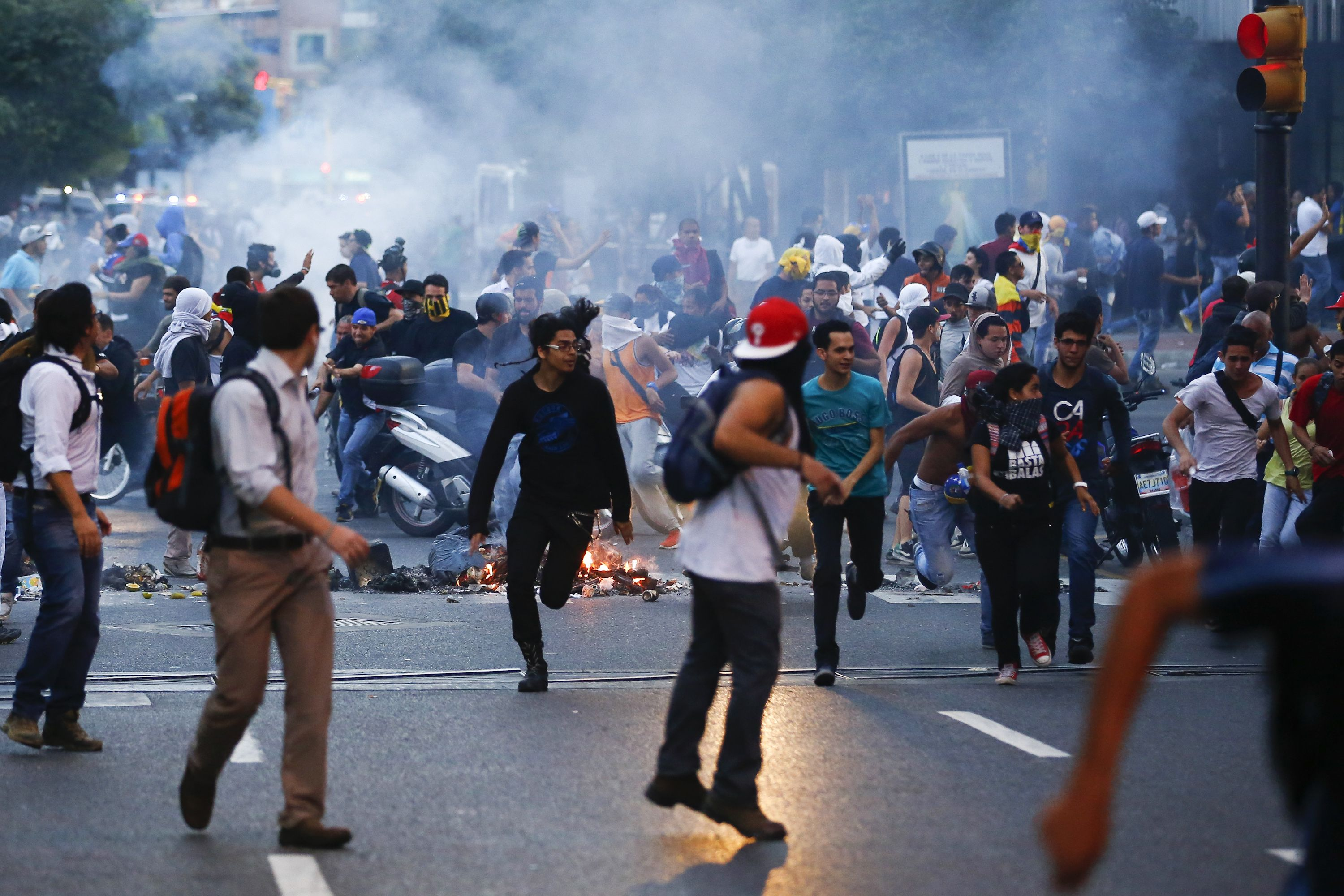 Demonstrators run away from tear gas during a protest in Caracas